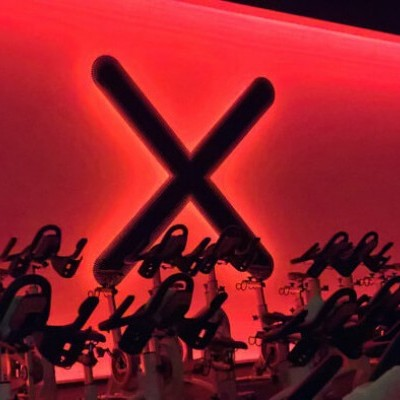 An X on the wall of an indoor cycling class is illuminated by deep red lighting.