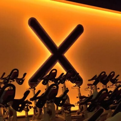 An X on the wall of an indoor cycling class is illuminated by deep orange lighting.