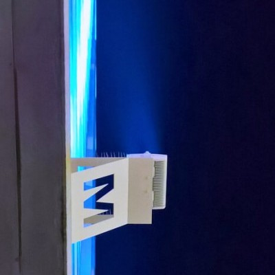 A slight side-view image looking  up at a building and it's M logo. Behind the logo, the buiding's exterior is lit by dark blue lighting.