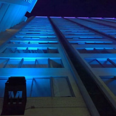 An image looking directly up at a building lit by dark blue lighting.