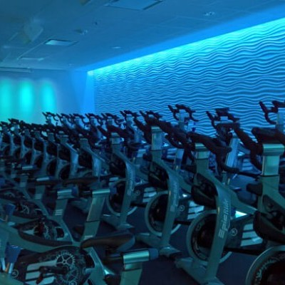 An indoor cycling studio illuminated by a mixture of dark and light blue lighting.