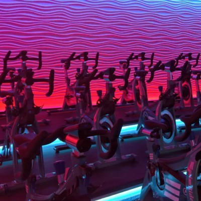 An indoor cycling studio with walls that are lit up with pink and blue lighting.
