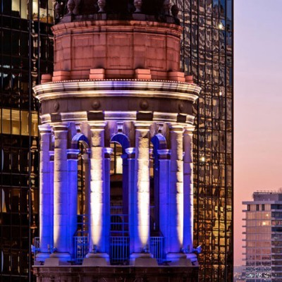 An external image of columns of a roof-top building being lit by dark blue lighting.