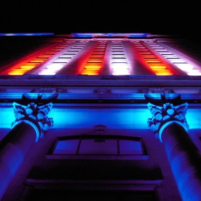An image looking up at a building illuminated in alternating red and white stripes of light.