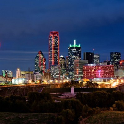 A landscape image of the city skyline lit up at night with careful lighting,