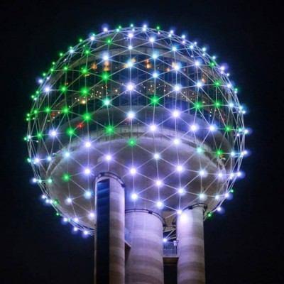 A sphere with dotted lights illuminating a mixture of white, green and occasionally red.